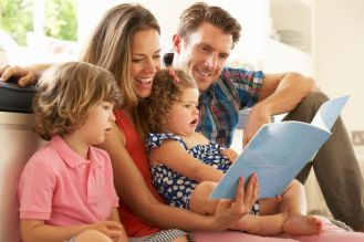 Parents-Sitting-With-Children-Reading-Story-Indoors