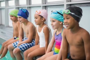 Cute swimming class smiling poolside at the leisure center
